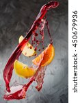 Small photo of Sangria ingredients flying in wine splashes