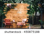Small photo of Wedding. Banquet. Mr. & Mrs. signs on wooden board decorated by flowers and greenery and lounge zone including chairs and tables.