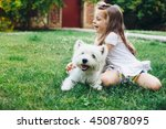 Stock photo child playing with english highland white terrier dog on grass in the backyard 450878095