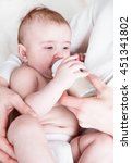 the baby in diapers eating milk ... | Shutterstock . vector #451341802