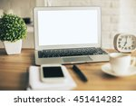 Closeup of creative designer desktop with blank white laptop, decorative plant, clock, blurry smartphone, coffee cup and stationery items. Mock up