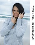 cute girl on the beach with gray hood. - stock photo