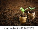 coins in soil with young plant. ... | Shutterstock . vector #451627792
