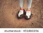 white sneakers in mud and soil... | Shutterstock . vector #451883356