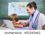 smiling teacher assisting boy... | Shutterstock . vector #452242462