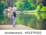 Young Boy Fishing From Wooden...