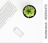 Small photo of White office desk table with wireless aluminum keyboard, smart phone in iphon style with blank screen and succulent flower in pot. Top view with copy space. Flat lay.