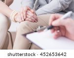 Small photo of Close-up of married couple's hands in an affectionate pose and a blurred flipboard with somebody writing on it