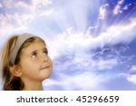 small girl looking at divine rays of light with expression of curiosity - stock photo