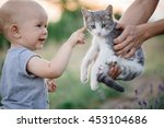 Child Playing With Cat In...