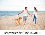 Stock photo back view of happy joyful young couple running on the beach with their dog 454106818
