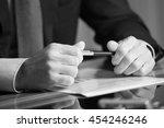 man's hands holding a black pen ... | Shutterstock . vector #454246246