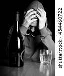 Small photo of young alcoholic in depression sitting at a table with a bottle of alcohol, black and white photo