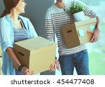 happy young couple unpacking or ... | Shutterstock . vector #454477408