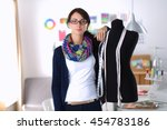 Small photo of Smiling fashion designer standing near mannequin in office