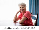 senior woman sitting at a table ... | Shutterstock . vector #454848106