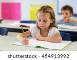 serious girl writing on book in ... | Shutterstock . vector #454913992