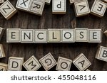 Small photo of the word of ENCLOSE on building blocks concept