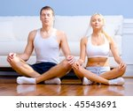 Young couple in sportswear sit on the floor meditating with closed eyes. Horizontal shot. - stock photo
