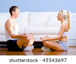 Young couple in sportswear face each other as they meditate on the floor. Horizontal shot. - stock photo