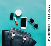 Small photo of Fashion concept : Flat lay of black leather woman bag open out with cosmetics, accessories and smartphone on green background