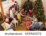 Small photo of A family are sat around a christmas tree, opening presents and pulling crackers.