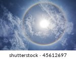 Sun with circular rainbow, clouds and blue sky - stock photo