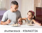 Little Girl And Father Are Having Meal Together - stock photo