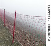Small photo of Rope Guard Fence From Red Netting Before Abyss In The Mountains In Foggy And Storm Weather On The Touristic Footpath