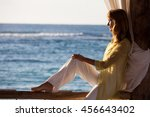woman sitting on a balcony at... | Shutterstock . vector #456643402