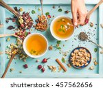 Stock photo two cups of healthy herbal tea with mint cinnamon dried rose and chamomile flowers in spoons and 457562656