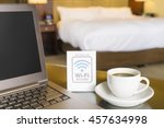 Stock photo hotel room with wifi access sign laptop and cup of coffee 457634998