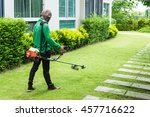 Man Worker Cutting  Grass With...