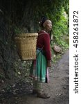 Small photo of Yuanyang, China-August 12, 2013: A Hani woman carries her goods up the road