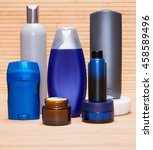 Small photo of Men's cosmetics. Face and body moisturizing creams, aftershave lotion, antiperspirant deodorant and other cosmetic products for men on wooden surface