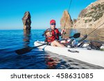 Fisherman on the boat kayak shows caught fish in the sea. Young man kayaking on fishing the bait near the island with mountains. - stock photo