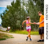Small photo of Boulder, Colorado, USA - July 24, 2016: Women's winner Maria Pobleta takes a cup of water at a run aid station during Tri Boulder.