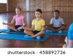 Stock photo school kids meditating during yoga class in basketball court at school gym 458892736