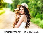 Stock photo pretty woman beautiful young happy with long dark hair in white dress holding small dog puppy 459163966