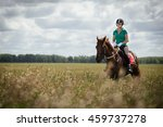 Stock photo young woman riding a horse on the green field 459737278