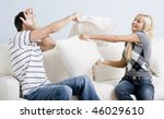 Young man holds his arm up in defense as a young woman playful hits him with a pillow. Horizontal shot. - stock photo