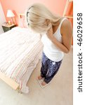 High angle view of woman standing in her bedroom and looking down at a scale. Vertical format. - stock photo