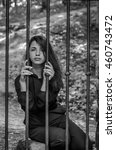 Small photo of Young charming woman with long hair offender, sits behind bars in the old stone jail prisoner and looks pityingly through steel bars