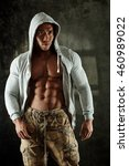 Small photo of Bodybuilder posing in hoody, showing perfect abdominal muscle.