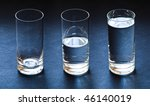 three glasses empty half and full with water on dark blue background - stock photo