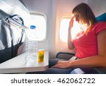 Small photo of Fear of flying woman in plane airsick with stress headache and motion sickness or airsickness. Focus on bottle and tablet.