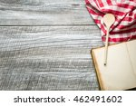 Cooking concept. Checkered napkin, wooden spoon and blank recipe book. - stock photo