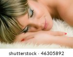 beautiful woman sleep on white fur - stock photo