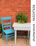 Small photo of Pretty little place to sit, with bright blue chair, white table and planter with healthy green flowering plants, all set against old red brick wall.