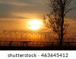 Silhouette Of A Tree And Fence...
